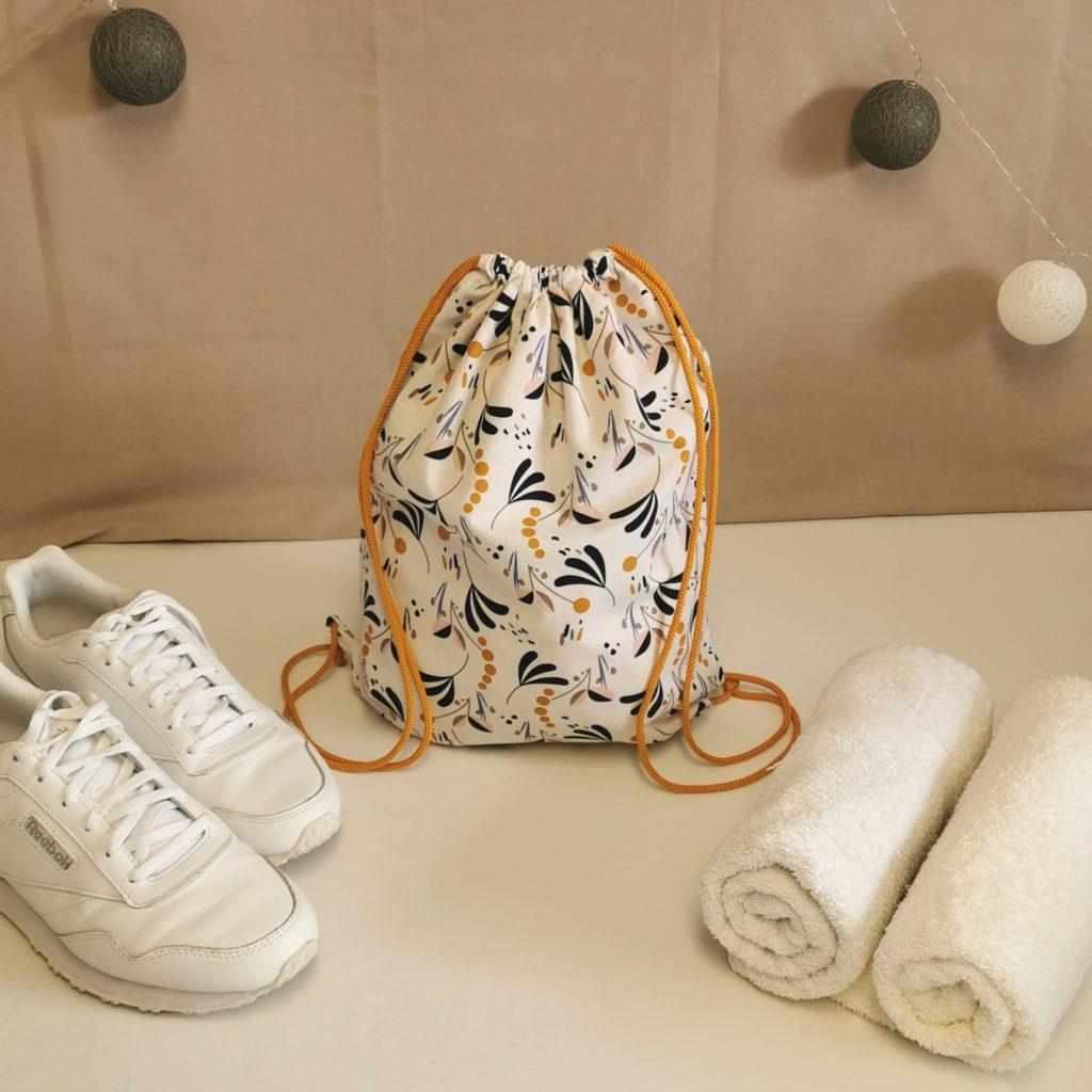 sac à chaussures blanc et jaune moutarde avec des motifs feuilles et pois bleu marine